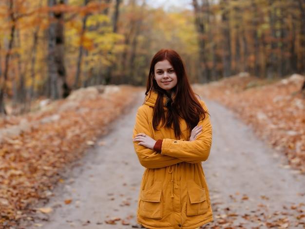 노란 재킷을 입은 야외 여성이 가을 숲길을 걷는다