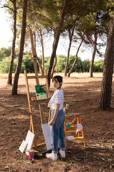 キャンバスに風景を描く自然の中で屋外の女性