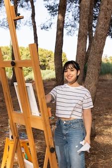 キャンバスに絵を描く自然の屋外の女性