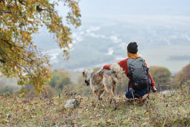 犬の隣の山で屋外の女性