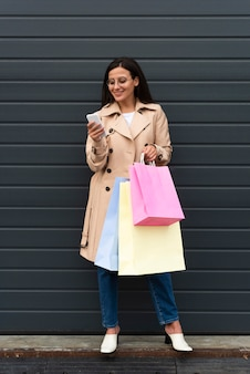 Woman outdoors looking at smartphone and holding shopping bags