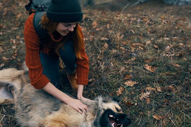 Женщина на открытом воздухе играет с собакой