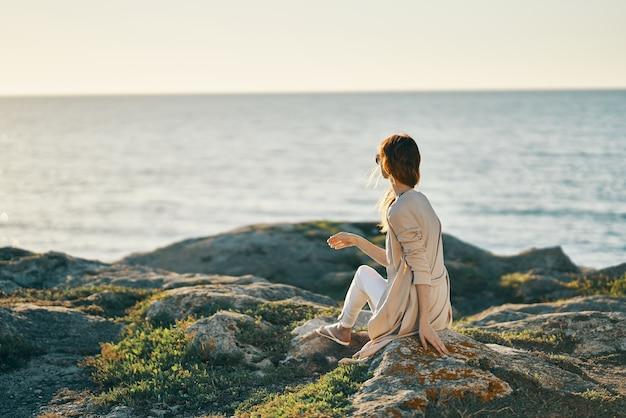 Женщина на открытом воздухе скалы океан путешествия летом