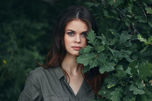 Женщина на открытом воздухе кусты с зелеными листьями смотреть вперед летом обрезанный вид