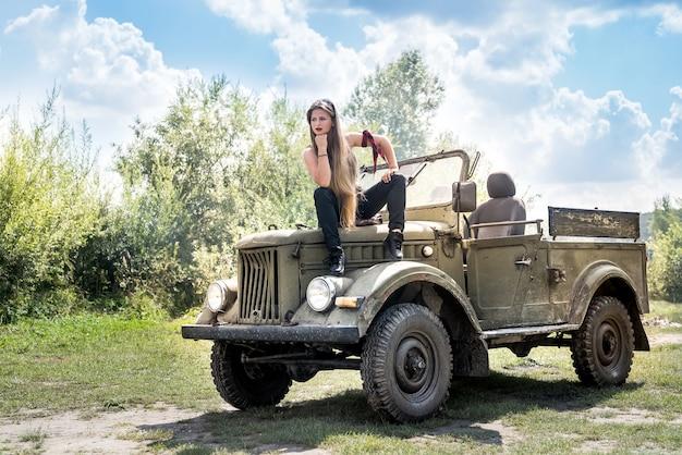 軍用車のボンネットに屋外で座っている女性