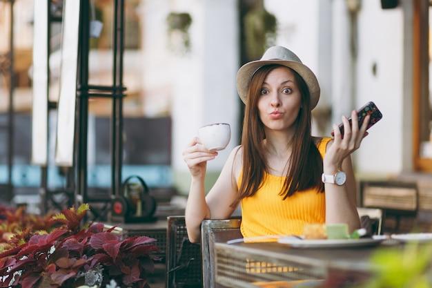 Donna in strada all'aperto caffetteria caffetteria seduta al tavolo in cappello con tazza di torta cappuccino, utilizzando il telefono cellulare, rilassante nel ristorante nel tempo libero