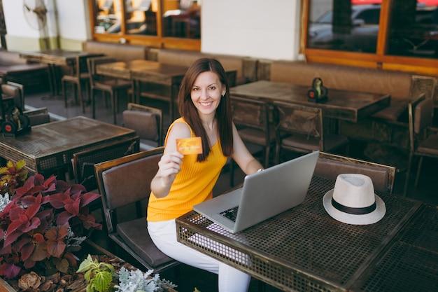 La donna in una caffetteria all'aperto di strada seduta al tavolo con un moderno computer portatile, tiene in mano una carta di credito