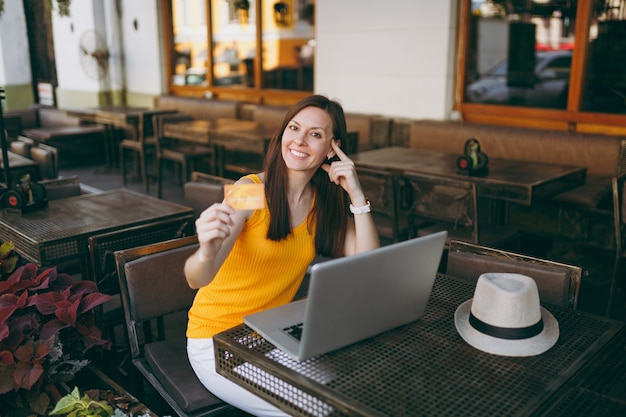 Woman in outdoors street coffee shop cafe sitting at table with modern laptop pc computer, holds in hand bank credit card