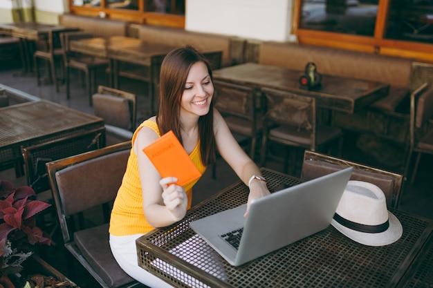 Donna in una caffetteria all'aperto di strada seduta al tavolo che lavora su un moderno computer portatile, tiene in mano il passaporto, prenota il biglietto aereo online