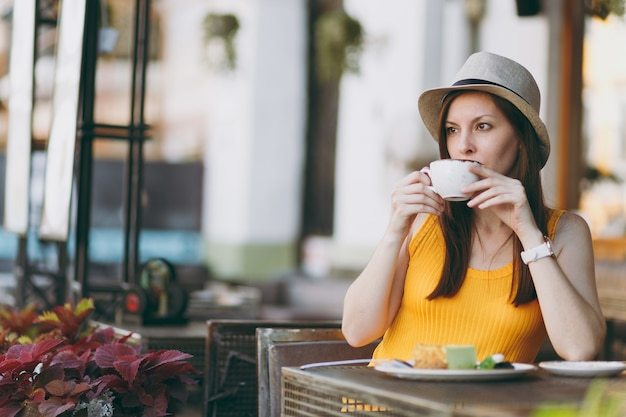 Woman in outdoors street coffee shop cafe sitting at table in yellow clothes hat with cup of cappuccino, cake, relaxing in restaurant during free time