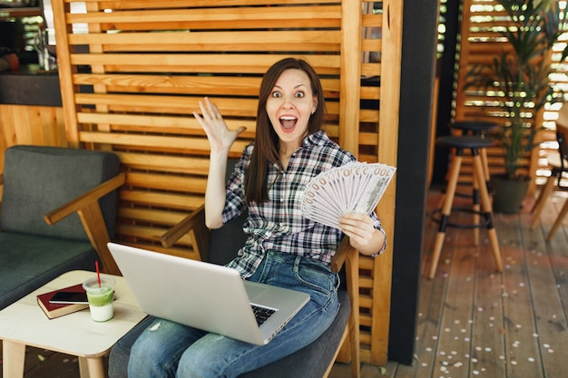 Woman in outdoors street coffee shop cafe sitting with modern laptop pc computer, hold in hand bunch of dollars banknotes, cash money