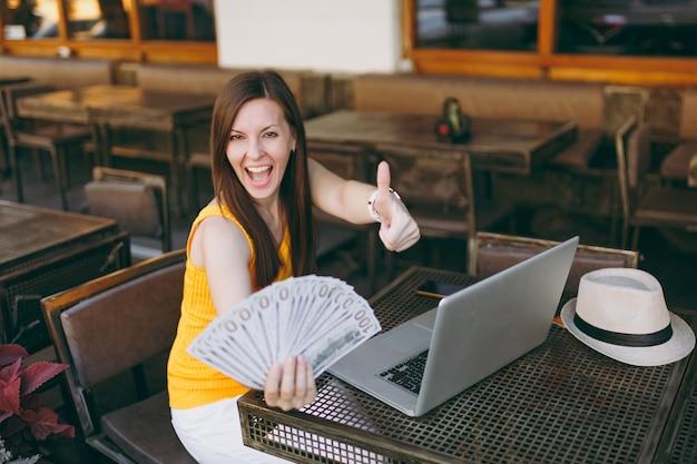 La donna in una caffetteria all'aperto di strada seduta con un moderno computer portatile, tiene in mano un mucchio di banconote in dollari
