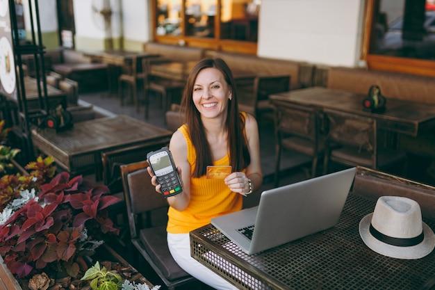La donna in una caffetteria all'aperto seduta con un computer portatile, tiene un moderno terminale di pagamento bancario wireless per elaborare i pagamenti con carta di credito