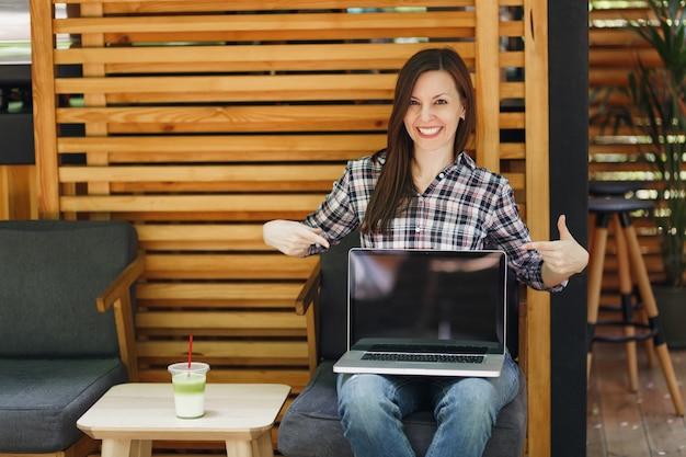 Donna in caffè all'aperto strada caffè in legno seduto in abiti casual, tenere il computer pc portatile con schermo vuoto vuoto, rilassarsi nel tempo libero. ufficio mobile