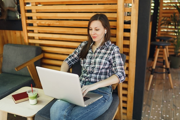 Woman in outdoors street summer coffee shop wooden cafe sitting in casual clothes, working on modern laptop pc computer