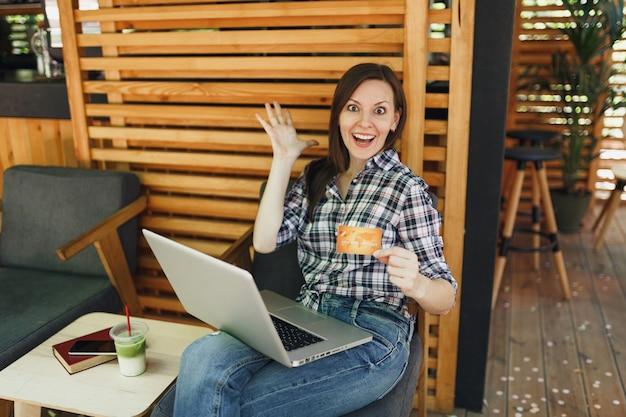 Donna in strada all'aperto caffè estivo caffè in legno seduto a lavorare su computer pc portatile, tenere la carta di credito bancaria rilassante durante il tempo libero