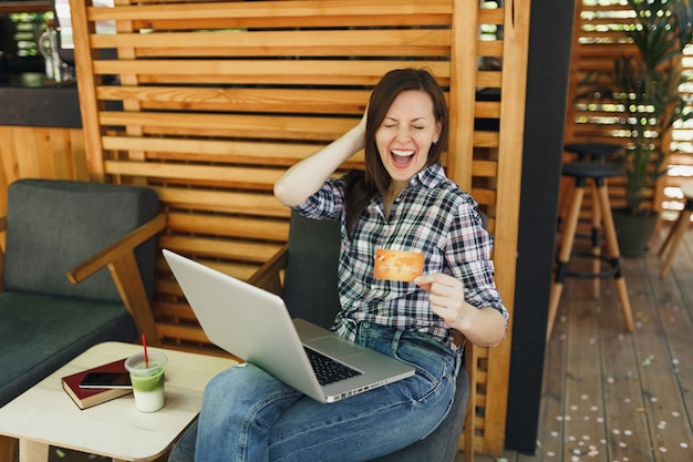 Woman in outdoors street summer coffee shop wooden cafe sitting working on laptop pc computer, hold bank credit card relaxing during free time