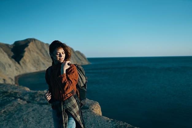 山の青い空への夏の屋外旅行の女性