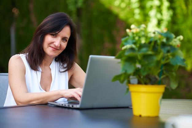 야외에서 카메라를 보며 노트북에 타이핑하는 여성