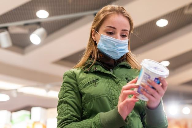 Woman outdoors wearing a mask looking at a yogurt