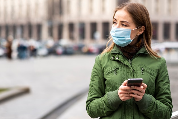 Woman outdoors wearing a mask and using the smartphone
