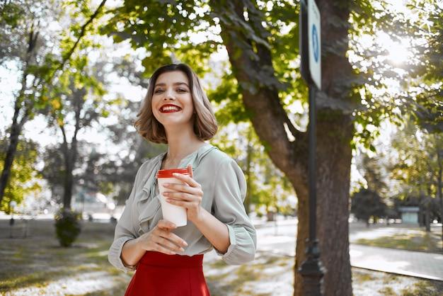 通りを歩いてコーヒーを飲みながら屋外の女性
