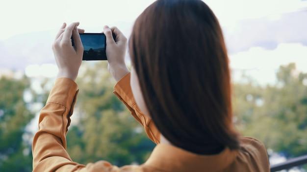 그녀의 손에있는 전화와 야외에서 여자는 카메라에 사진을 찍습니다.