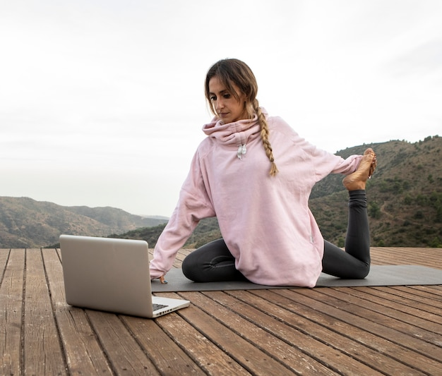 ヨガをしているラップトップを持つ屋外の女性
