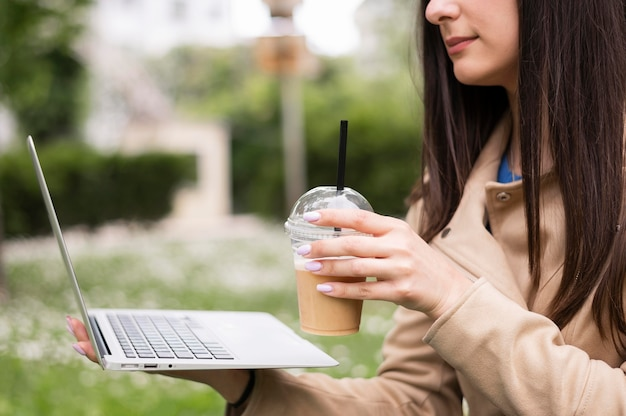 Woman outdoors working on laptop while having a drink