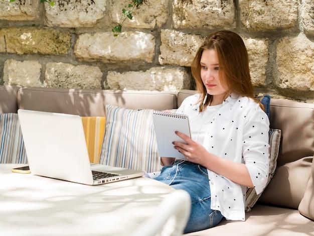 ノートパソコンとイヤホンを扱う屋外の女性