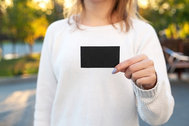 검은 종이 사각형을 들고 밖에 서 여자