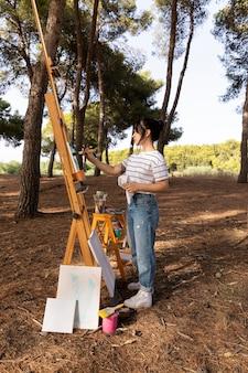 キャンバスに絵を描く自然の外の女性