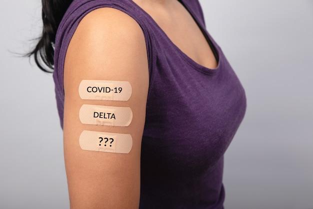 灰色の背景の上の女性は、コロナウイルスワクチン、新しいスタンプの概念、突然変異covid-19の後に肩に多くの絆創膏を示しています