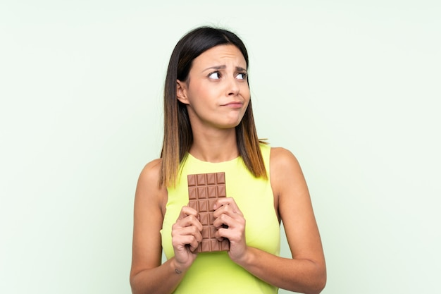 チョコレートタブレットを取り、疑問を持つ緑の壁の上の女性
