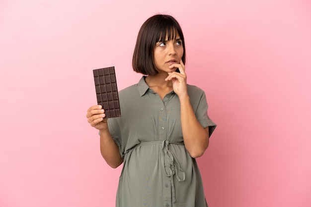 Женщина на изолированном фоне беременна и сомневается, держа шоколад