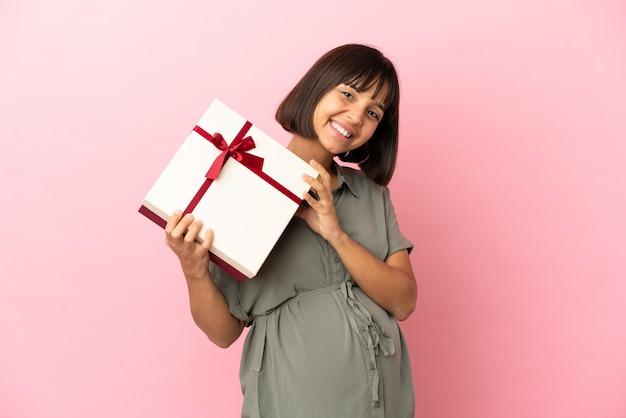 Женщина на изолированном фоне беременна и держит подарок