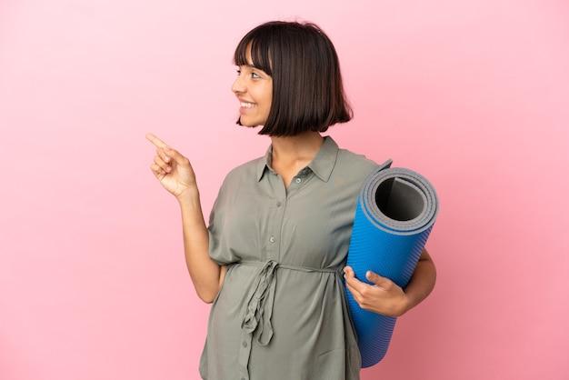 Женщина на изолированном фоне беременна и держит циновку, представляя что-то
