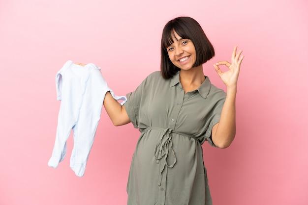 妊娠中の孤立した背景の上の女性とokサインで赤ちゃんの服を保持しています