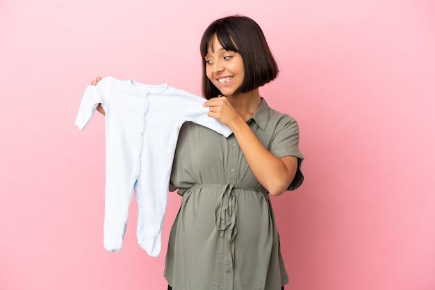 Женщина на изолированном фоне беременна и держит детскую одежду