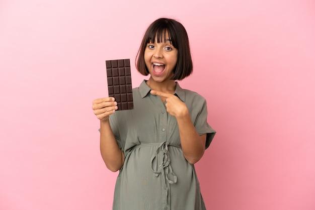 妊娠し、チョコレートを保持している孤立した背景上の女性