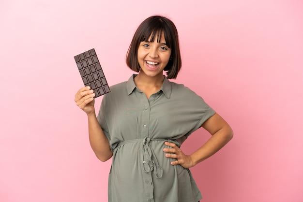 Женщина на изолированном фоне беременна и держит шоколад