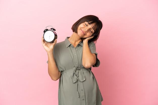 妊娠し、睡眠ジェスチャーをしている時計を保持している孤立した背景上の女性