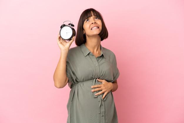 妊娠し、ストレスの多い表現で時計を保持している孤立した背景上の女性