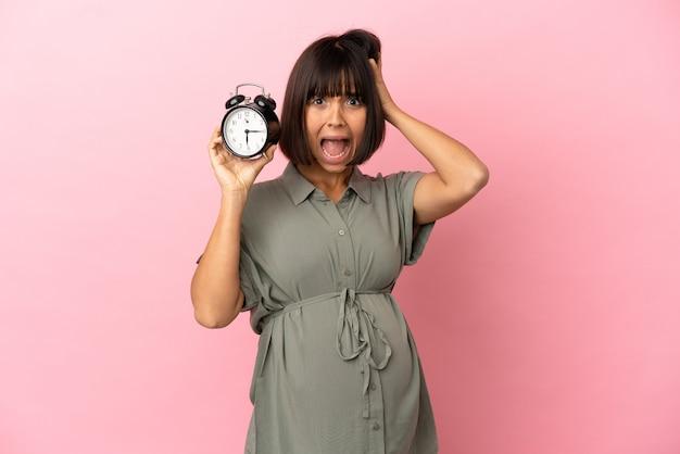 Женщина на изолированном фоне беременна и держит часы с удивленным выражением лица