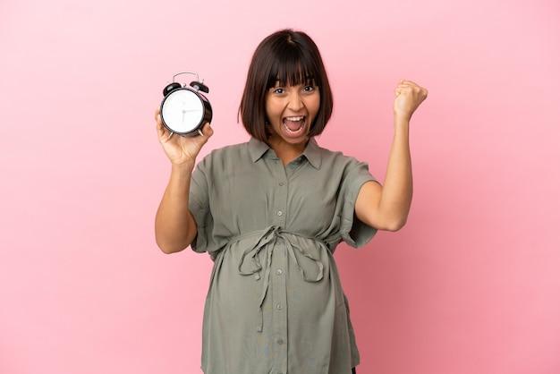 Женщина на изолированном фоне беременна и держит часы