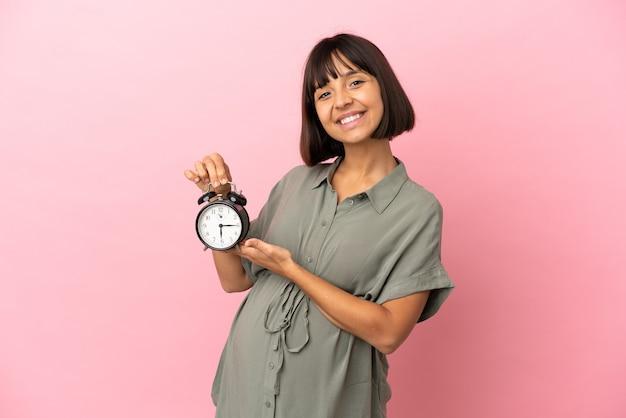 Женщина на изолированном фоне беременна и держит часы Premium Фотографии