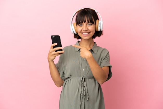 妊娠中の孤立した背景と携帯電話で音楽を聴いている女性