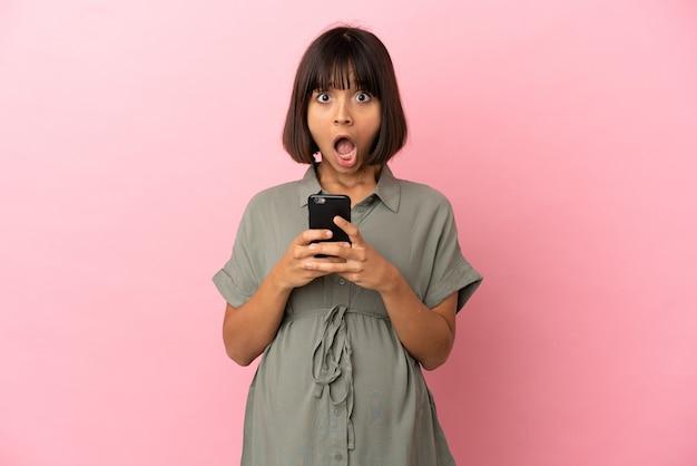 妊娠し、驚いた表情で携帯電話を使用して孤立した背景上の女性