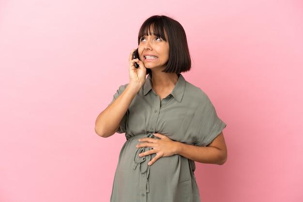 妊娠し、携帯電話を使用して孤立した背景上の女性