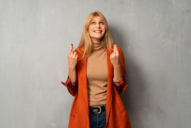 Женщина на текстурированном фоне с пальцами, пересекая и желая лучшего